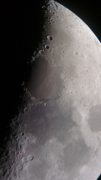 The moon taken with a mobile phone camera through the eye piece of a telescope